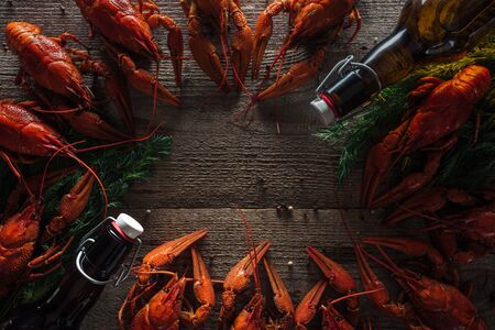 top view of red lobsters, dill and glass bottles with beer on wooden surface
