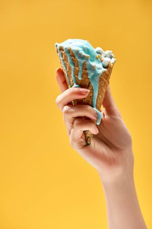 partial view of woman holding delicious melted blue ice cream in crispy waffle cone isolated on yellow