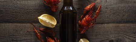 panoramic shot of red lobsters, lemon slices and glass bottle with beer on wooden surface