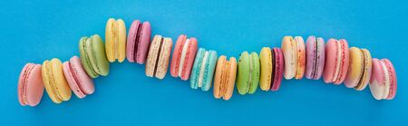 top view of multicolored delicious French macaroons in curved line on blue bright background, panoramic shot