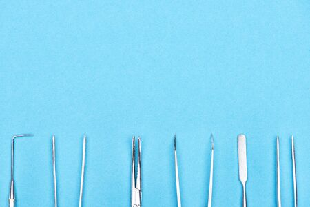 top view of set with metallic dental instruments isolated on blue Banco de Imagens