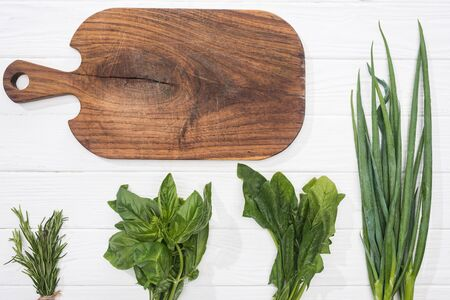 top view of wooden cutting board and greenery on white table