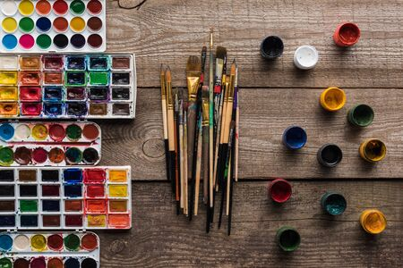 top view of colorful paint palettes on wooden brown surface with paintbrushes and gouache