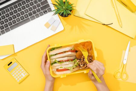 cropped view of woman holding lunch box near laptop and office supplies