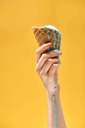 cropped view of woman holding delicious melted blue ice cream in crispy waffle cone isolated on yellow Archivio Fotografico