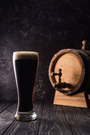 glass of beer near small brown keg with tap on wooden table
