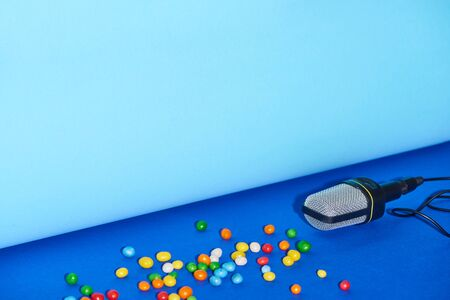black microphone and candies on bright and colorful background with copy space