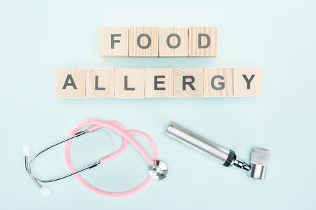 top view of pink stethoscope near wooden blocks with food allergy lettering and dermatoscope on blue background