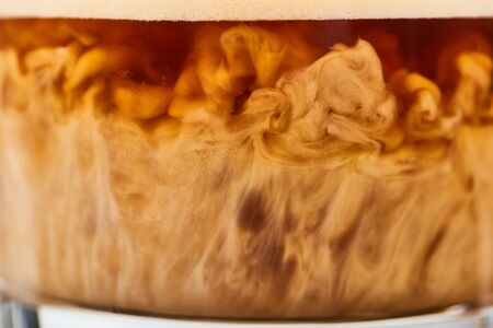 close up view of coffee mixing with milk in glass