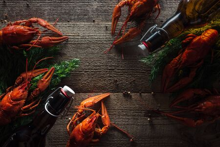 top view of red lobsters, dill and bottles with beer on wooden surface