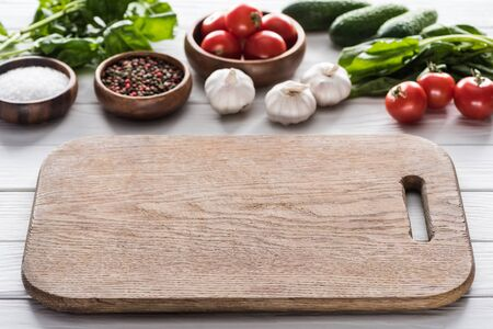 selective focus of cutting board, cherry tomatoes, greenery, garlics, cucumbers, salt and spices