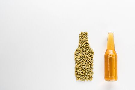 top view of bottle of light beer near pressed hop isolated on white