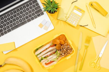 top view of lunch box with food near laptop and office supplies