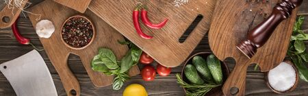 panoramic shot of cutting boards, cherry tomatoes, salt, garlic, cucumbers, chili peppers, pepper mill, meat chopper, lemon and spices
