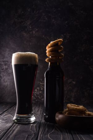 glass and bottle of beer with fried onion rings in bowl on wooden table Foto de archivo - 130306666