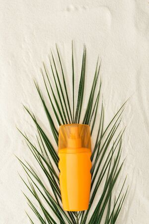 top view of palm leaf and orange sunscreen on sand Stock Photo
