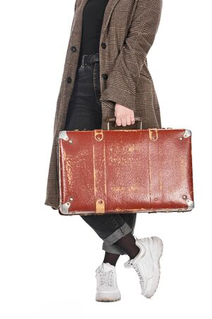 cropped view of woman in plaid coat with crossed legs holding vintage weathered suitcase isolated on white Stockfoto