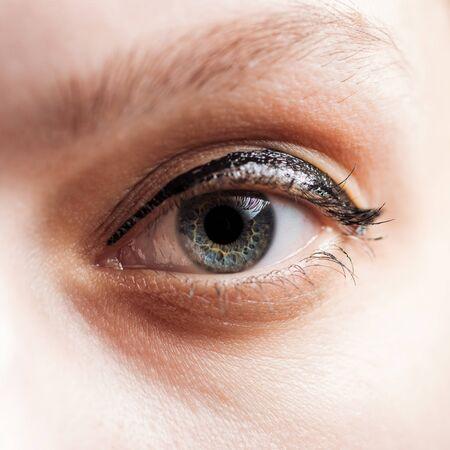 close up view of woman blue eye looking at camera