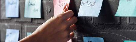 cropped view of woman attach colorful sticker pads with notes on black brick wall