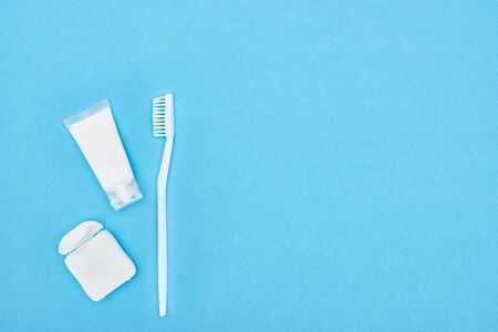 top view of toothbrush and toothpaste near teeth floss isolated on blue Stock Photo