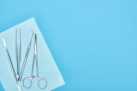 top view of metallic set with dental tools on apron isolated on blue 写真素材 - 130305776