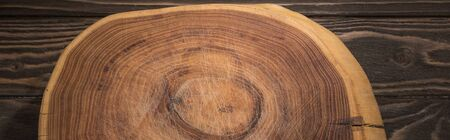 panoramic shot of wooden cutting board on brown table