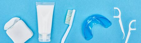 panoramic shot of toothbrush, toothpaste and teeth floss near retainer and floss sticks isolated on blue