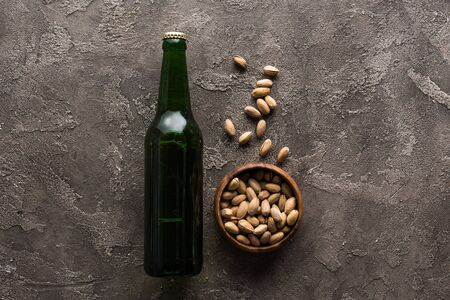 top view of bowl with pistachios near green bottle of beer on brown surface