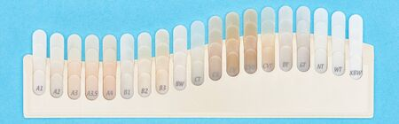 panoramic shot of teeth samples with different shades isolated on blue 写真素材