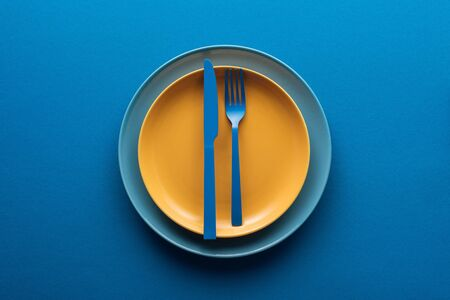 top view of blue plastic knife and fork on yellow plate above another plate on blue background
