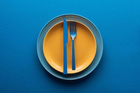 Vista superior del cuchillo y tenedor de plástico azul en placa amarilla encima de otra placa sobre fondo azul. Foto de archivo