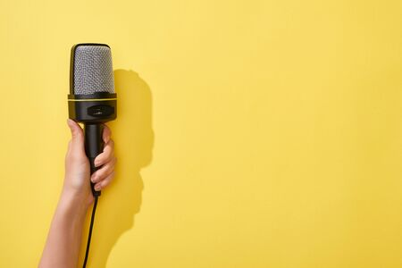 cropped view of woman holding microphone on yellow background