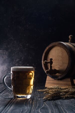 mug of light beer near small keg and wheat spikes on wooden table