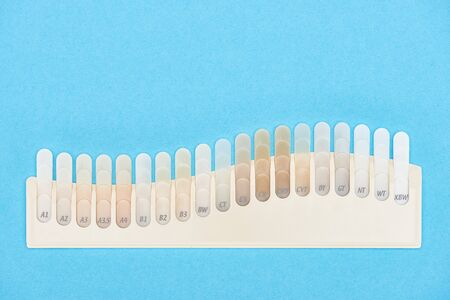 top view of teeth samples with different shades isolated on blue 写真素材