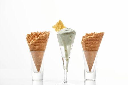 fresh crispy sweet waffle cones and pistachio ice cream isolated on white Imagens