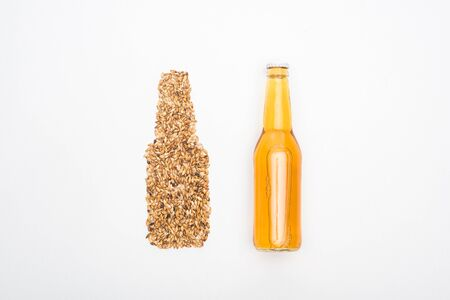 top view of bottle of light beer near whole wheat grains isolated on white