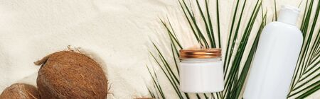top view of cosmetics with coconuts and palm leaves on golden sand, panoramic shot