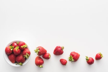 top view of sweet and whole strawberries on bowl on white background