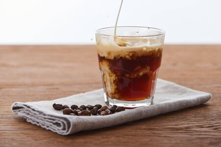 milk pouring into ice coffee in glass on napkin with coffee grains on wooden table isolated on white