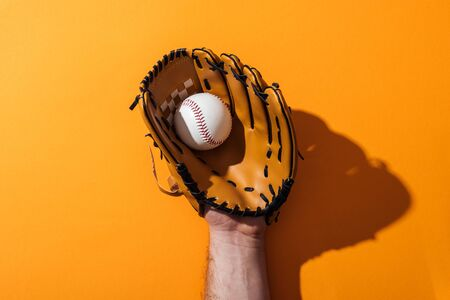cropped view of man holding softball in brown baseball glove on yellow