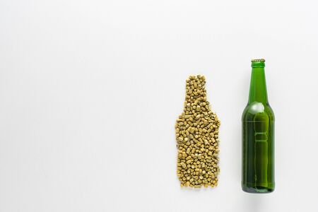 top view of bottle of beer near pressed hop isolated on white