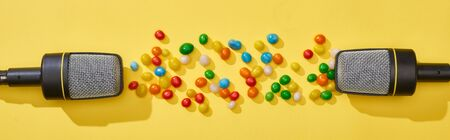 panoramic shot of microphones and candies on bright and colorful background 版權商用圖片