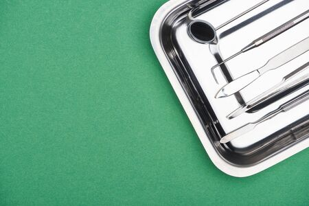 top view of set with dental instruments in metallic plate isolated on green Banco de Imagens