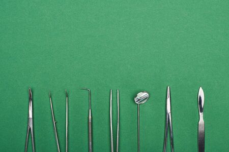 top view of set with stainless dental tools isolated on green Banco de Imagens