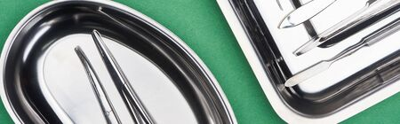 panoramic shot of set with dental tools in metallic plates isolated on green