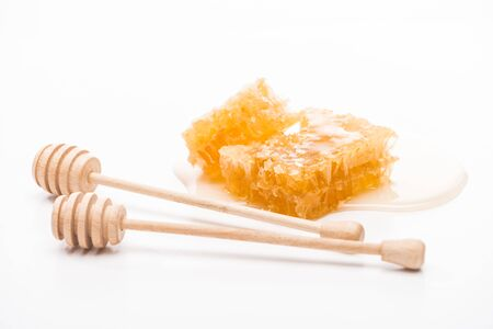 honeycomb with honey near wooden honey dippers on white background