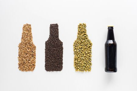 top view of bottle of dark beer near wheat, coffee grains and pressed hop isolated on white Stock Photo