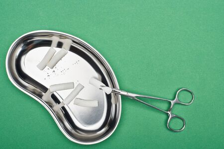 top view of scissors near metallic plate with cotton pads isolated on green