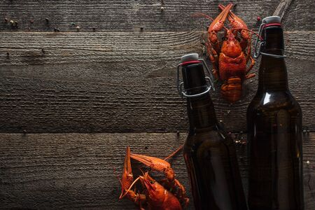 top view of red lobsters and bottles with beer on wooden surface