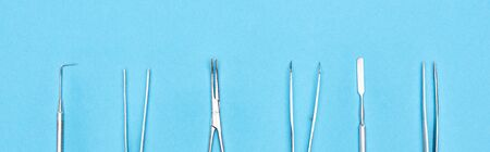 panoramic shot of set with metallic dental instruments isolated on blue 写真素材 - 130304874